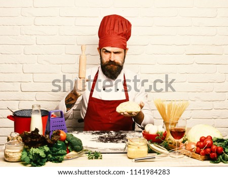 Cook with strict face in burgundy uniform sits by table with vegetables and kitchenware. Chef makes dough. Italian cuisine concept. Man with beard holds dough and rolling pin on white brick background #1141984283