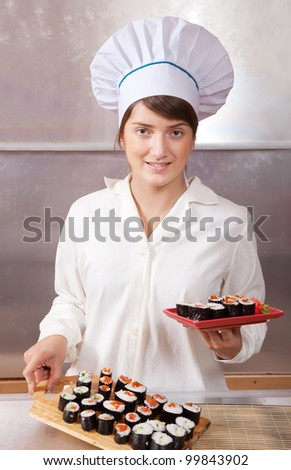 Cook woman with cooked  sushi rolls in kitchen