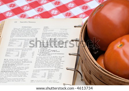 Cookbook of tomato recipes next to a basket of my fresh garden tomatoes.