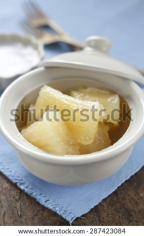cooked casava or yucca in syrup serve with tiny cup of coconut milk. thai desseert. thai dessert in thai style bowl on cotton blue cloth on old wooden table.