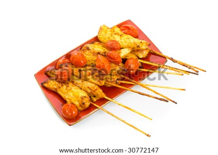 Cooked chicken tenderloin skewers isolated over white background.