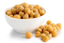 Cooked chickpeas in white bowl on white. Spilled chickpeas.