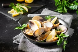 Cooked clams in a black ceramic plate on the black kitchen table. Seafood dish