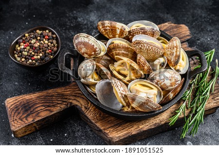 Cooked Clams vongole in a pan. Black background. Top view. Сток-фото ©