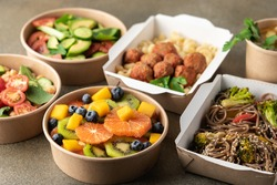 Cooked food in paper eco-friendly containers. Food delivery for home or office. Vegetable, fruit salads and noodles