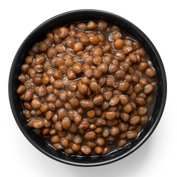 Cooked french green puy lentils in black ceramic bowl isolated on white. Top view.