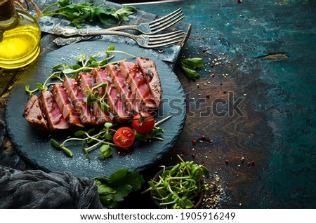 Cooked juicy tuna steak with vegetables on a black stone plate. Restaurant food. Seafood. Rustic style. Flat Lay.