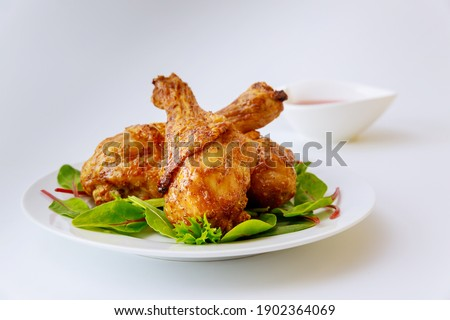 Cooked legs of chicken with spinach on white plate. Balanced meal. Stok fotoğraf ©