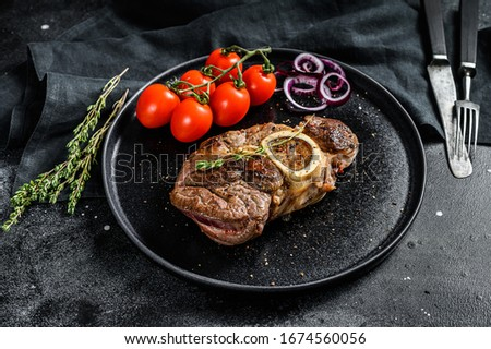 Cooked meat on the bone Osso Buco in tomato sauce. OssoBuco meat stew. Black background. Top view Foto stock ©