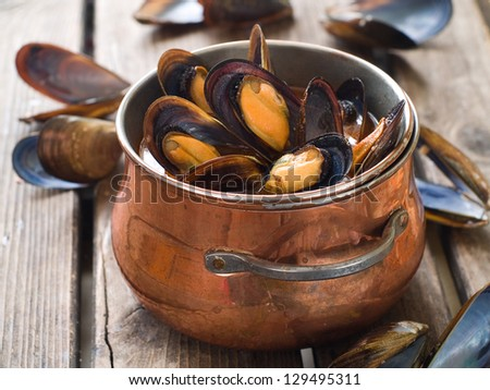 Cooked mussels in a copper pot, selective focus