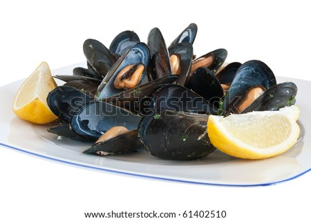 cooked mussels on a plate with lemon isolated with clipping path