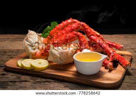 Cooked Organic Alaskan King Crab Legs with Butter and lemons,Alaskan King Crab on vintage wooden background. #778258642