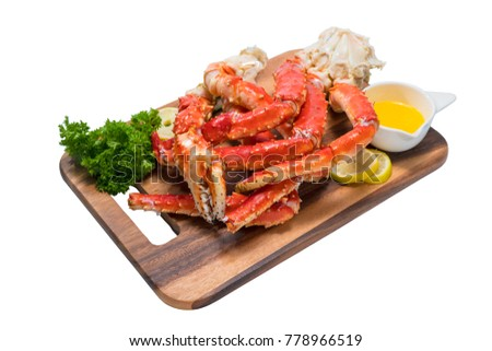 Cooked Organic Alaskan King Crab Legs with Butter and lemons,Alaskan King Crab on wood plate in white background. #778966519