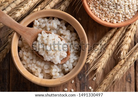 Cooked peeled barley grains in wooden bowl on wooden table