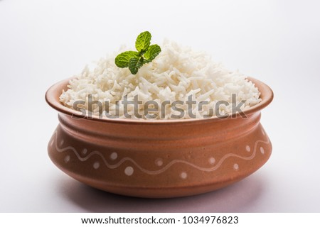 Cooked plain white basmati rice in terracotta bowl over plain or wooden background