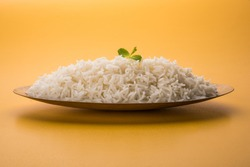 cooked plain white basmati rice served in a brass bowl or plate, isolated over colourful or wooden background