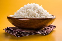 cooked plain white basmati rice served in a wooden bowl, isolated over colourful or wooden background