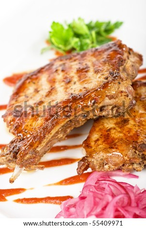 Cooked pork chop with kiwi and parsley on a white