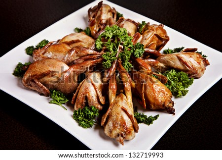 Cooked quail served on plate with parsley