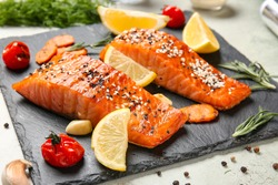 Cooked salmon fillet and vegetables on slate plate