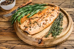 Cooked salmon fillet with herbs and pink pepper. wooden background. Top view