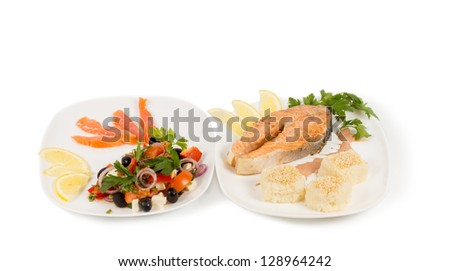 Cooked salmon steak and salad served on two seperate plates