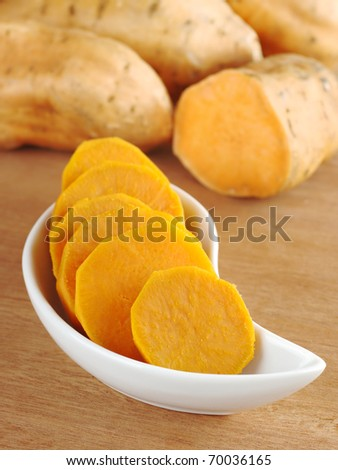 Cooked sweet potato (lat. Ipomoea batatas) cut in slices in white bowl on wooden surface with sweet potatoes in the background (Selective Focus, Focus on the front of the bowl)