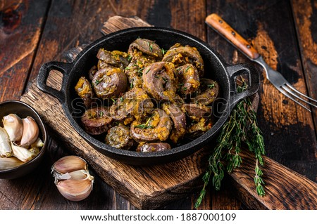 Cooked turkey hearts offals with herbs. Dark wooden background. Top view. Foto stock ©