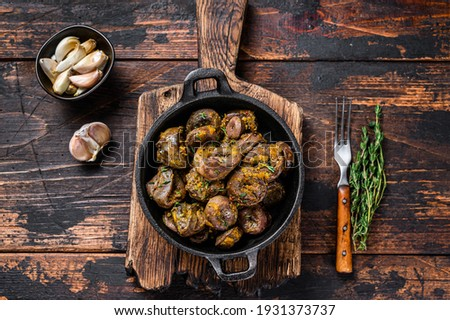 Cooked turkey hearts offals with herbs. Dark wooden background. Top view. Photo stock ©
