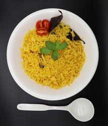 Cooked turmeric jasmine rice with powdered curcumin or Haldi, Indian food, indian basmati rice homemade with tomato and Cardamom.