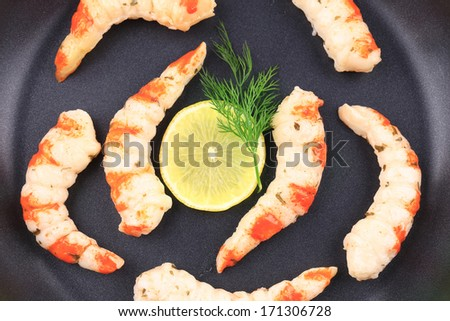 Cooked unshelled shrimps on frying pan. Whole background.
