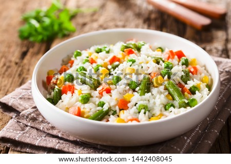 Cooked white rice mixed with colorful vegetables (onion, carrot, green peas, corn, green beans) in white bowl (Selective Focus, Focus in the middle of the dish)