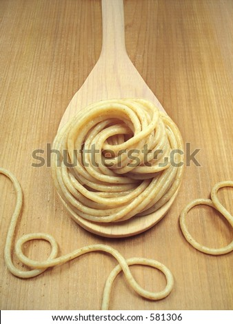 Cooked whole wheat pasta on wooden spoon