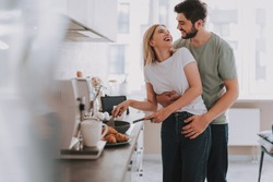 Cooked with love. Cute laughing blonde frying something in skillet. Her bearded husband is hugging her from behind