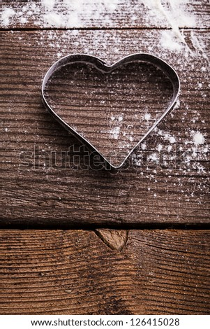 Cookie cutter heart shape on the kitchen table and flour