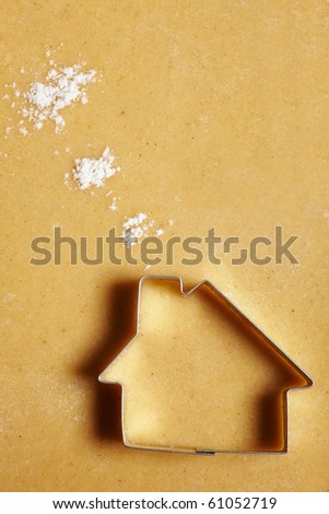 Cookie cutter house on dough with flour clouds