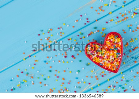 Cookie cutter with candy sprinkles, top view. Multicolored candy sprinkles on blue wooden background. Happy Valentines Day.