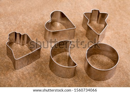 Cookie cutters on a sheet of baking paper #1560734066