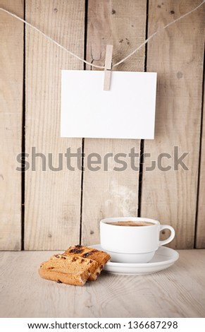 cookies and cup of coffee in front of a wooden wall with blank note paper hanged