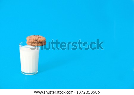 cookies and glass of milk on blue background. oatmeal cookie with pieces of chocolate #1372353506
