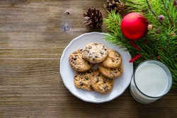 Cookies and milk for Santa Clause on wood background, copy space
