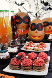Cookies brains of marzipan on a table with a variety of sweets in honor of Halloween