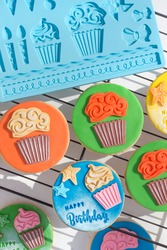 Cookies decorated for birthday party. Fondant craft. Colored cupcakes.
