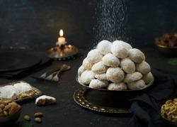 Cookies for celebration of El Fitr Islamic Feast( The Feast that comes after Ramadan).Sprinkling powdered sugar on Kahk (Eid-Al- Fitr cookies).