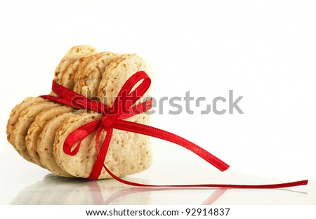 Cookies-hearts connected by a red tape on a white background - stock photo