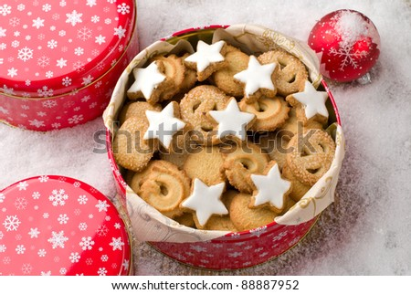 Cookies in a tin and christmas ball on a wooden background covered with snow