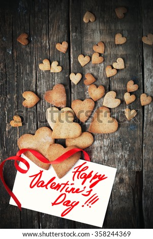 Cookies in Shape of Hearts for Valentine\'s Day. Cards with Pastry, Message Isolated on White and Red Ribbon on Wooden Table. Valentines theme