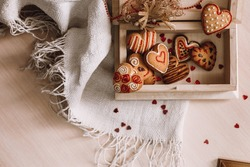cookies in the shape of hearts with a color pattern in a wooden box on a light decoration fabric with small hearts. Valentine's Day card. composition, background