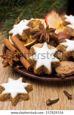 cookies in the shape of stars with icing and spices on a wooden table, close up, vertical
