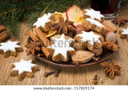 cookies in the shape of stars with icing and spices on a wooden table, horizontal